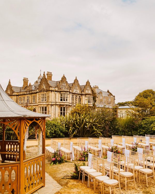 wooden gazebo with wedding chairs in rows, set in the garden of a stately home which is in the background.