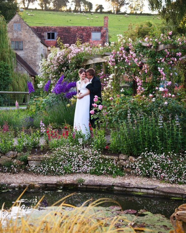 wedding couple in traditional wedding clothes embracing in a garden. In the foreground is a pond, in the background are old fashioned rose bushes and an old mill building.