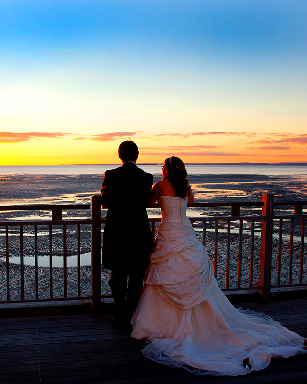 couple in traditional wedding clothes looking out to sea, standing on the balcony of a pier with iron railings
