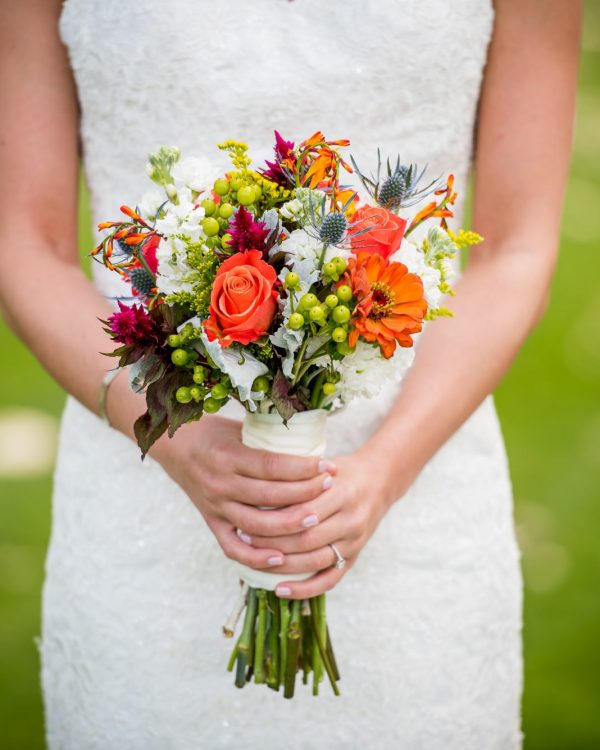 bride holding bright coloured bouquet