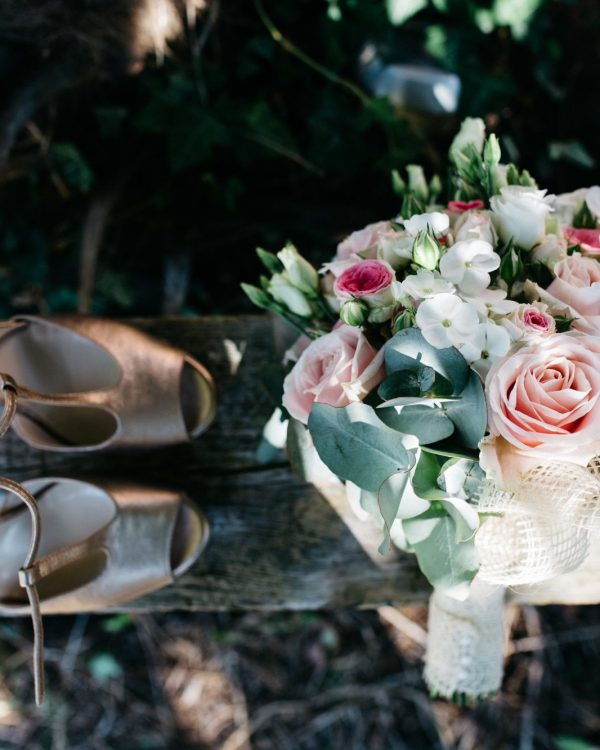 wedding shoes and bouquet on rustic plank