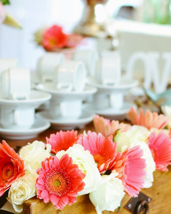 gerbera flowers with coffee cups on bar