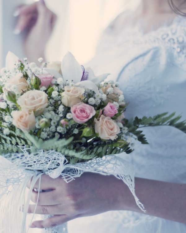 bride by windown with bouquet