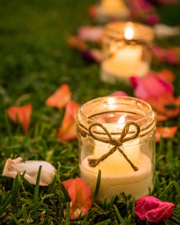 candle in jar on grass with petals