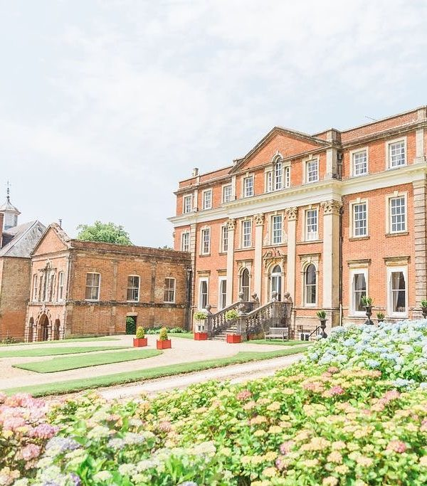 grand georgian red brick country house, viewed from an angle across the gardens.
