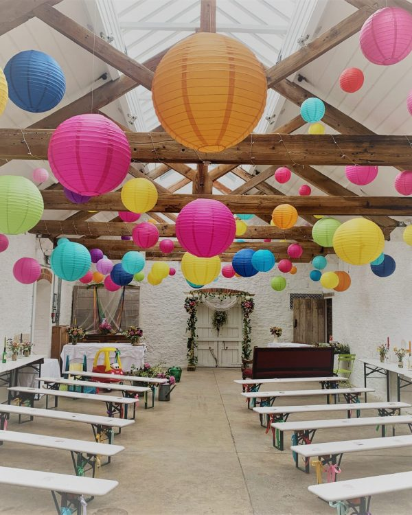 white painted hall with timber beams. benches either side of an aisle. ceiling decorated with lots of coloured paper globes