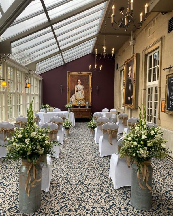 orangery with sloping roof, laid out with white chairs forming an aisle. 2 floral decorations stand either side of the aisle, and the walls are decorated with gold framed oil paintings
