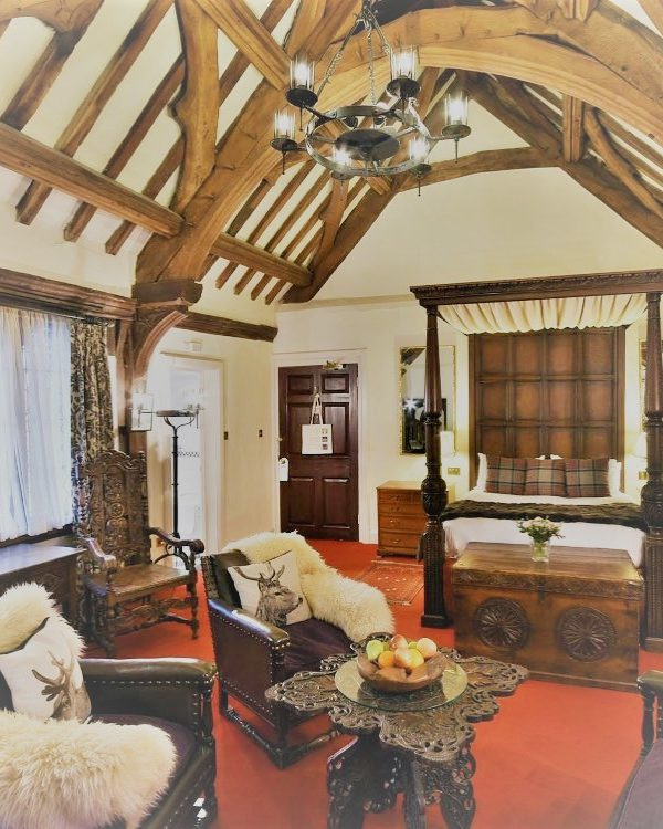 grand bedroom with arched oak beams. There is a dark wood 4 poster bed, a rich red carpet and leather seating.