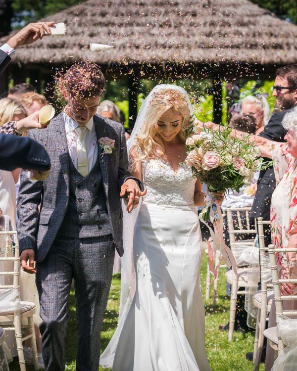 Set in a garden with a wooden gazebo in the background, young wedding couple walking down aisle after ceremony with guests throwing confetti.