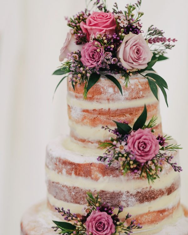 naked wedding cake with pink roses