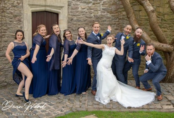 wedding party in fun pose in front of castle door
