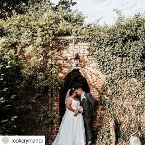 couple kissing under brick arch