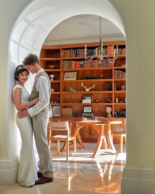 young wedding couple standing in archway with library shelves in background