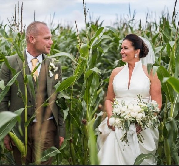 wedding couple standing in field of green corn that is higher than their heads, looking at each other and smiling