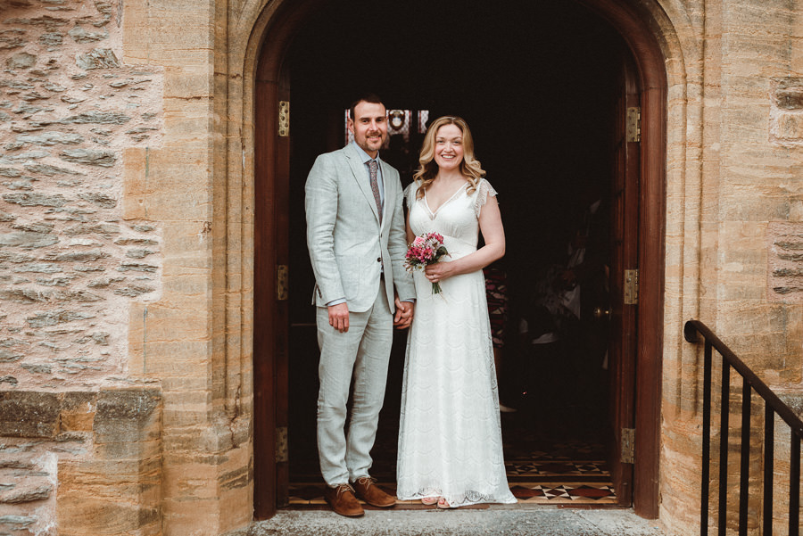 just married couple in suit and white dress standing in arched stone doorway