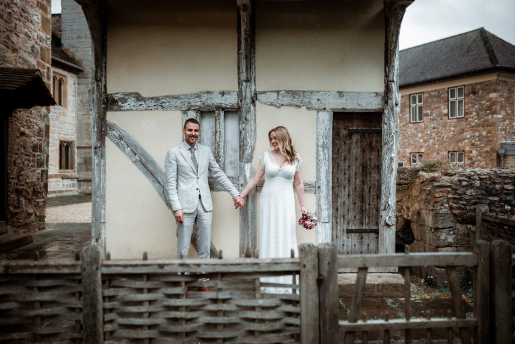 wedding couple holding hands in candid pose in front of small medieval cottage in grounds of museum courtyard