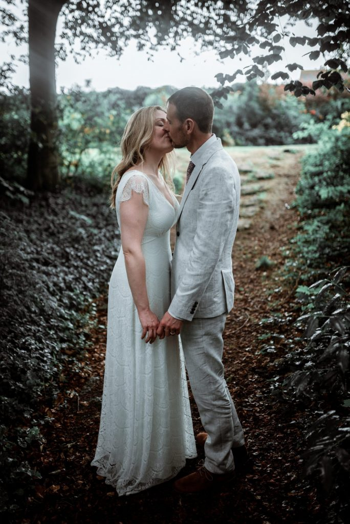 couple in wedding dress and suit kissing while stood on a woodland path in autumn
