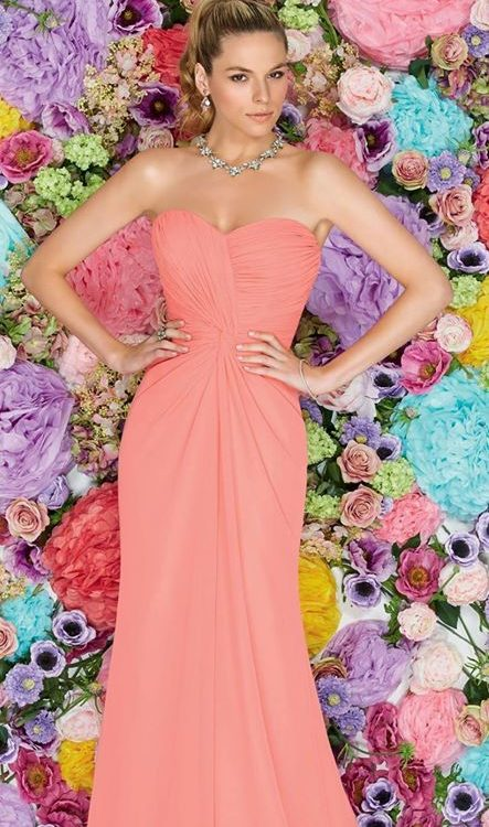 woman wearing pink bridesmaid gown in front of multicolour floral wall