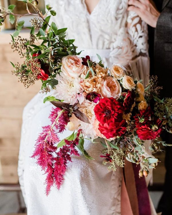 bride holding bouquet of pink and red flowers