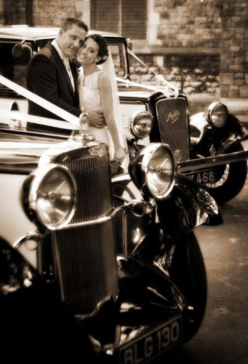 bride and groom standing between 2 vintage cars