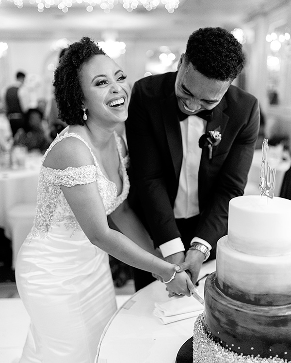 couple laughing and cutting wedding cake