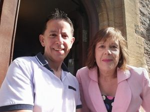 man with short dark hair wearing light shirt with woman wearing pink jacket and mid length brown hair, looking happy