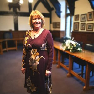 woman in burgundy dress smiling and standing in a tudor ceremony room at Taunton register office