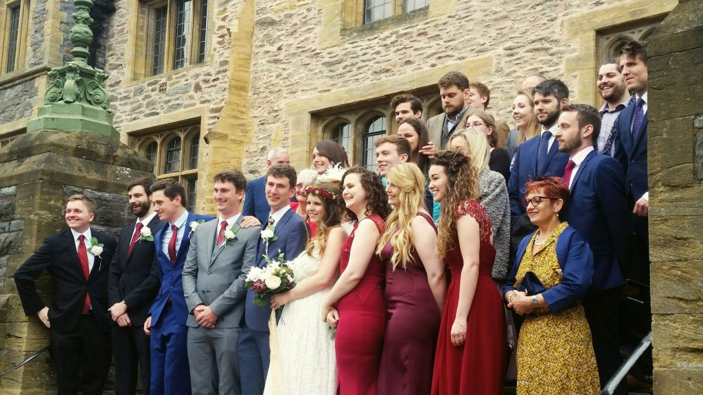wedding couple and guests standing on steps posing for group photos outside tudor stone building.