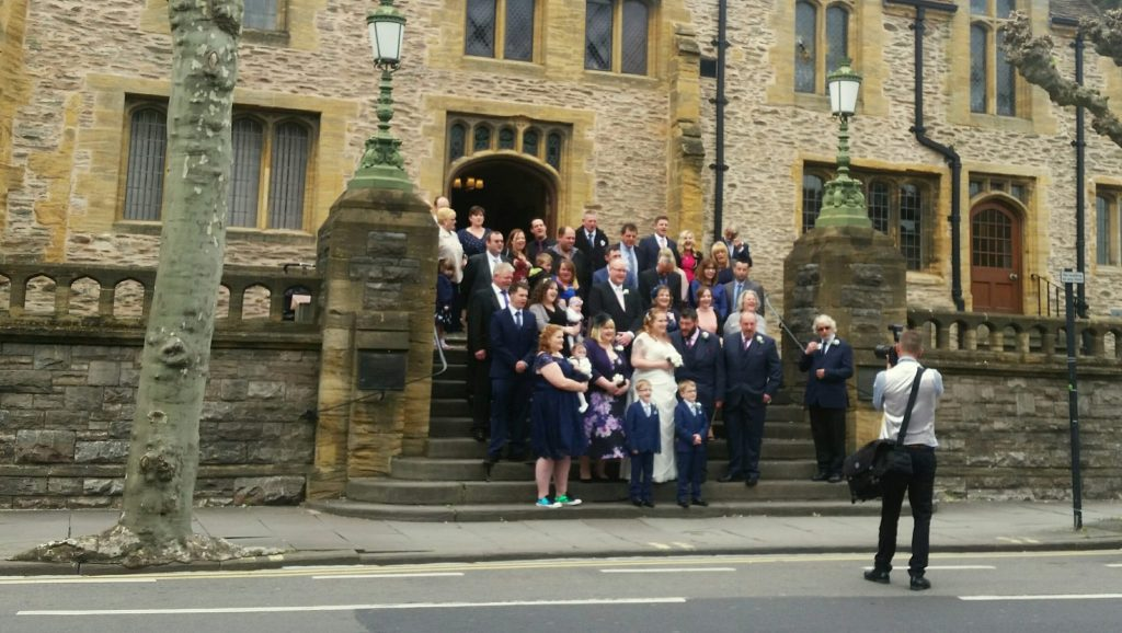 wedding party posing for photos on steps outside stone building, with a photographer taking shots in the foreground