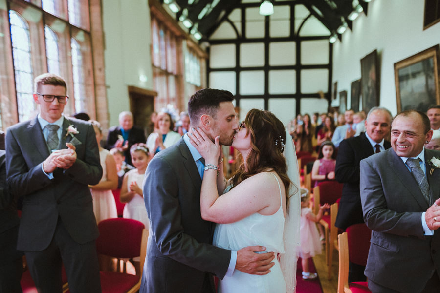 just married couple kissing with guests applauding standing an oak beamed tudor hal
