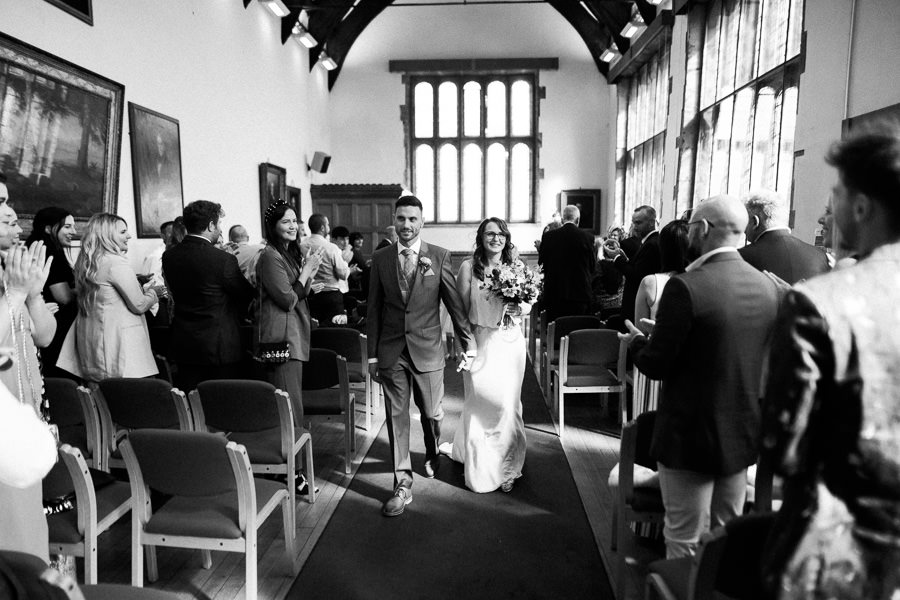 black and white image of couple walking back down aisle after getting married, surrounded by standing guests in an oak beamed tudor hall