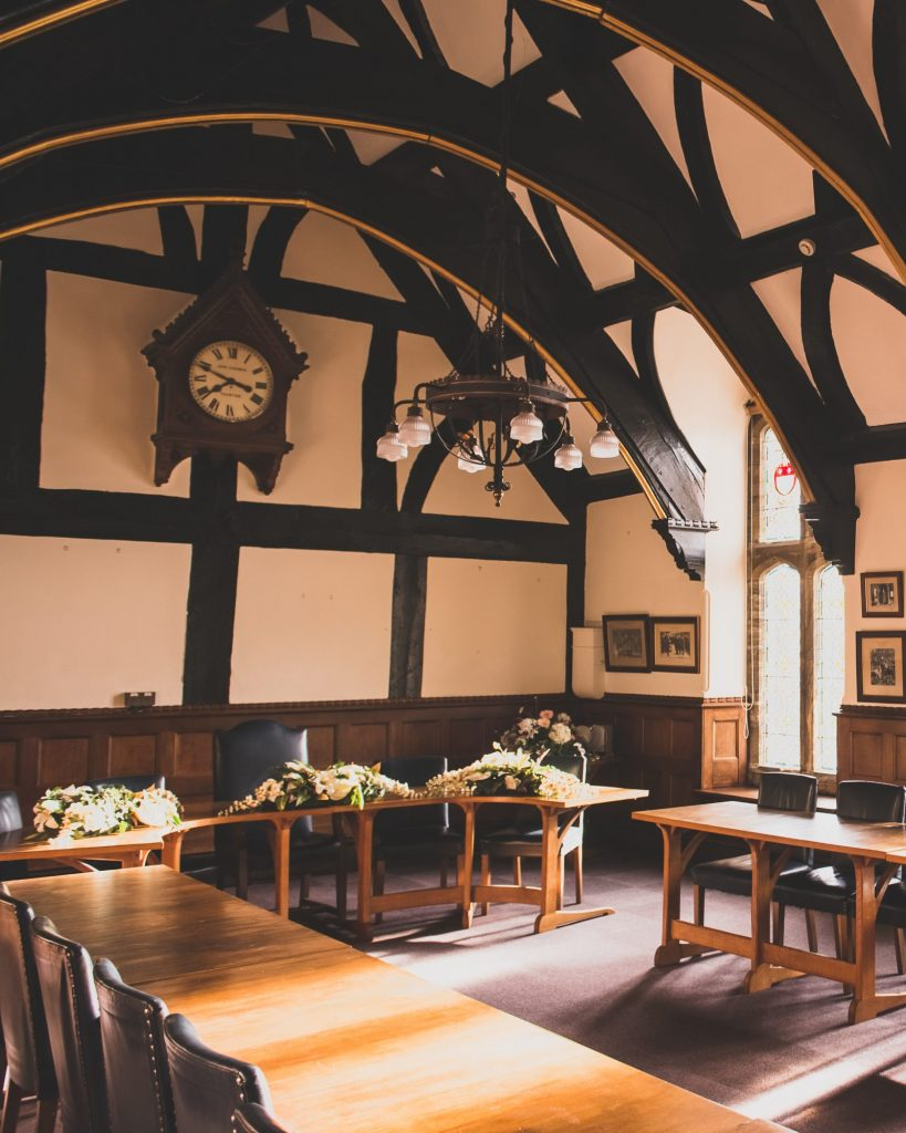 image of tudor ceremony room with vaulted oak beamed ceiling, oak tables and blue leather chairs and a large antique clock hanging high on the wall