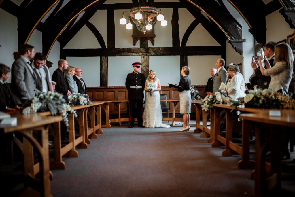 married couple, bride in white dress and groom in military uniform, standing with registrar during wedding ceremony. guests line either side of the room which has vaulted oak beamed ceiling.