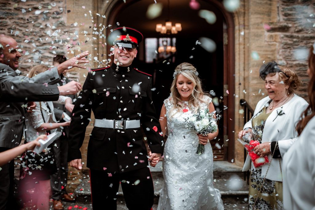 couple in white dress and military uniform exit ceremony building with guests throwing confetti