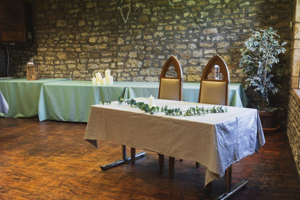 wedding ceremony setting - table with white cloth and leaves and candle, with 2 medieval style chairs behind. Bare stone walls in background