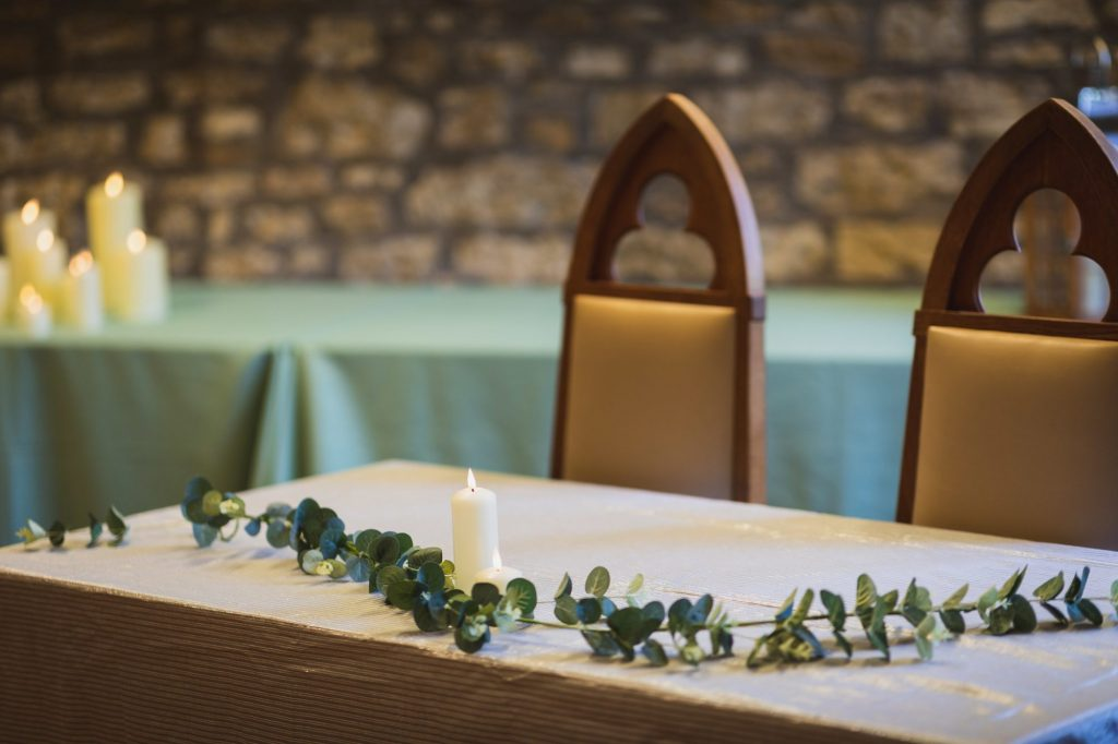 ceremony setting with white clothed table decorated with leaves and candle, and 2 medieval style chairs behind it