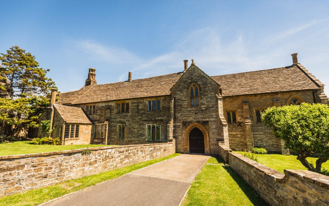 medieval manor building with grass lined drive