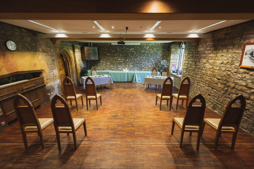 ceremony room with old bare stone walls, medieval style chairs either side of a wood floored aisle.